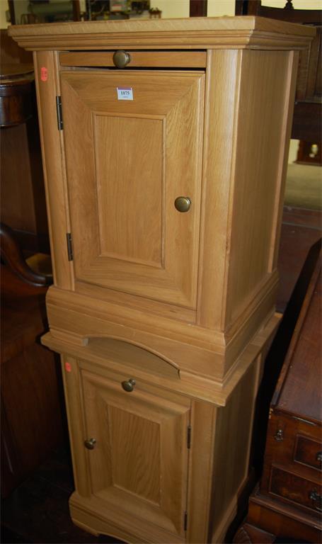 A pair of contemporary light oak single door bedside cupboards