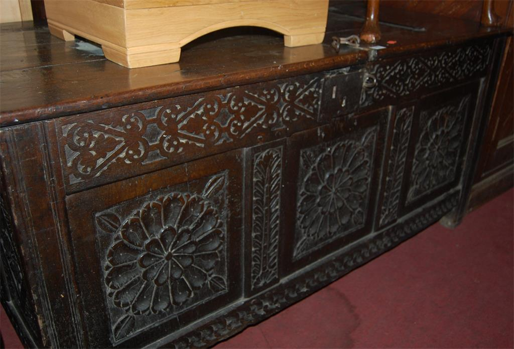 A late 17th century low relief carved oak three panelled hinge-top coffer