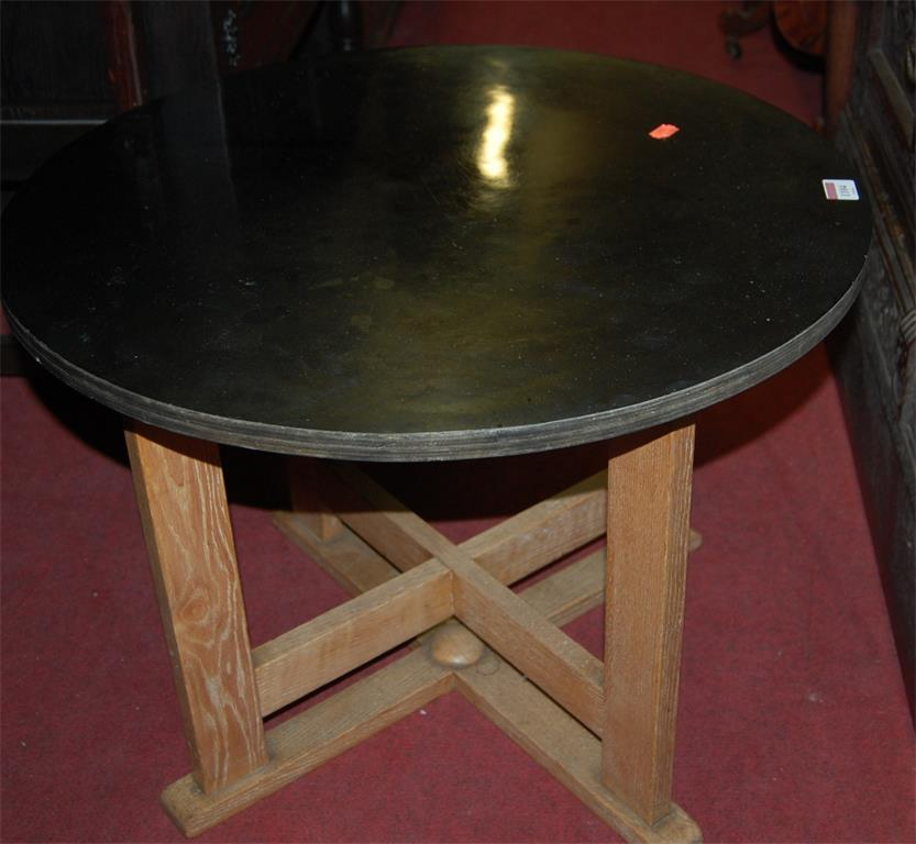 A 1930s circular laminate topped and light oak based low occasional table