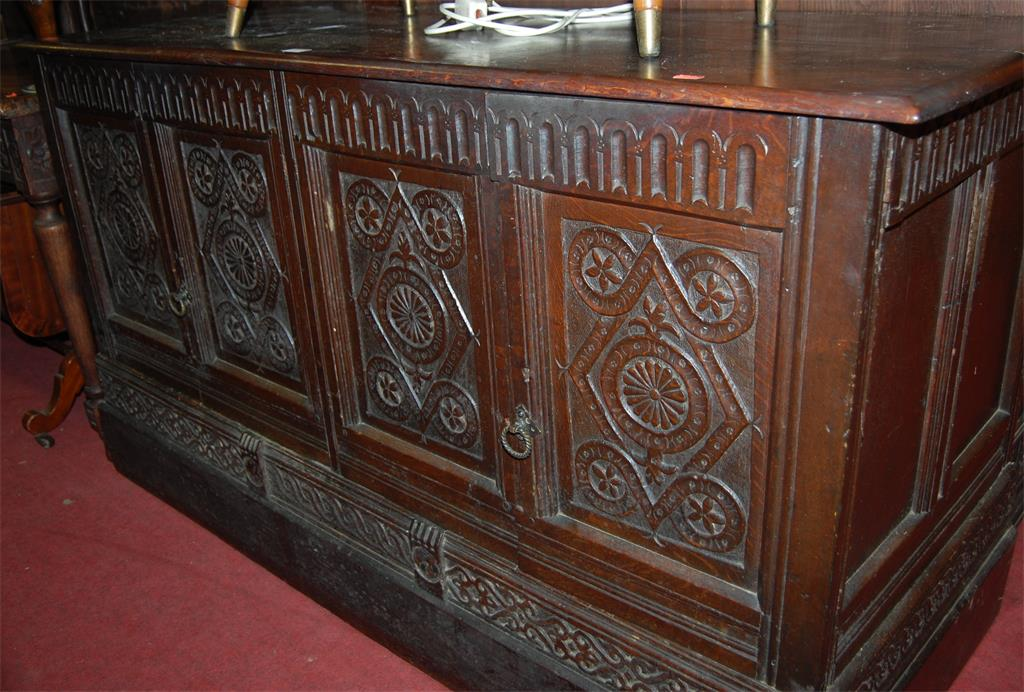 An 18th century and later converted low relief four panel carved oak four door mule chest