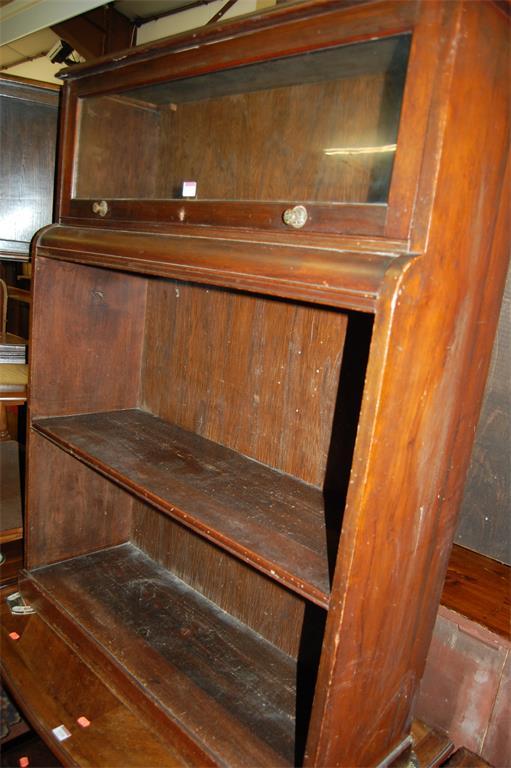 An Edwardian walnut ledgeback open bookshelf, having upper hinged glazed door