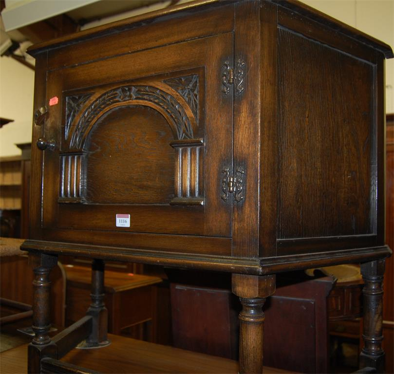 A 17th century style moulded oak single door credence shaped cupboard