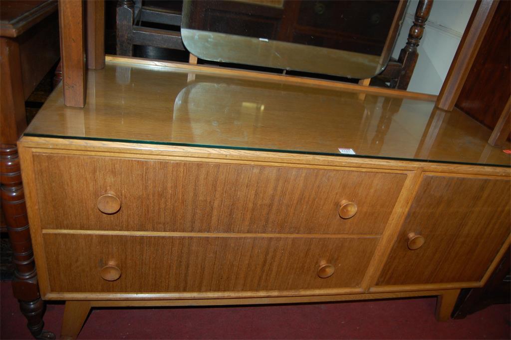 A 1950s light oak mirrorback dressing table