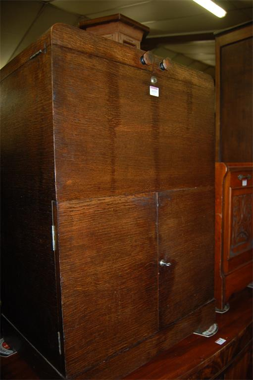 An Art Deco oak drinks cabinet, the twin hinged fold-out top opening to reveal rising bottles