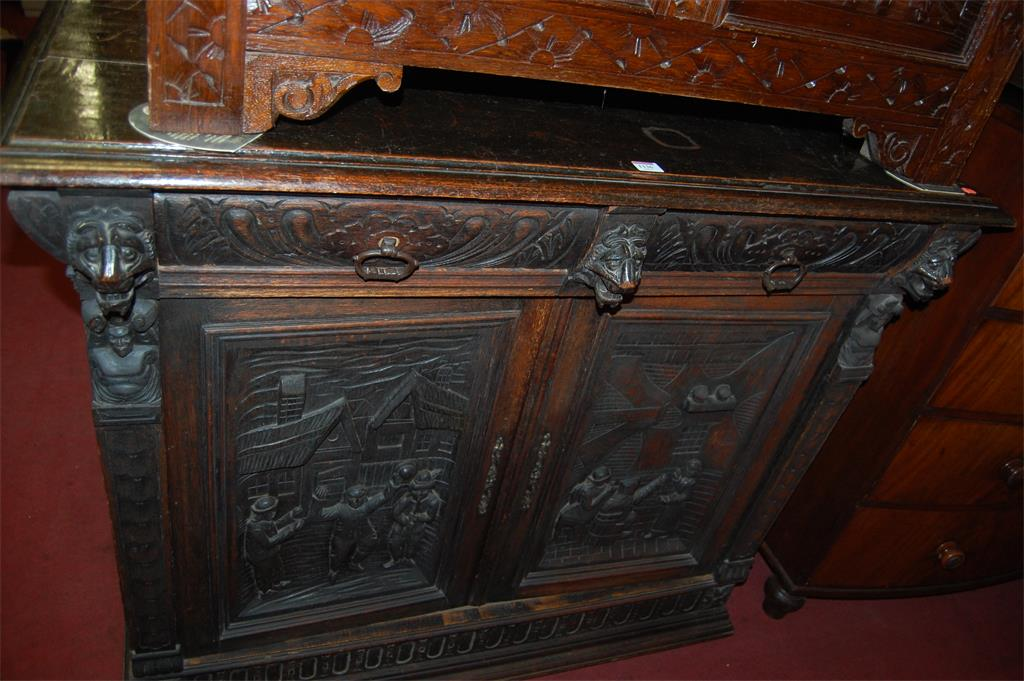 A late 19th century continental carved oak double door side cupboard, having twin frieze drawers with lion mask detail