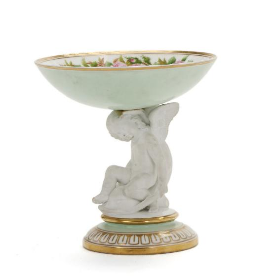 A porcelain bowl decorated in colours and gold the figure in biscuit