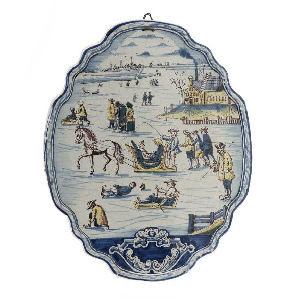 Dutch 18/19th century faience shield shaped plaque decorated in colours with winter landscape with people skating and riding can