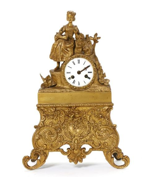 A French gilt bronze figural mantel clock with white enamel dial