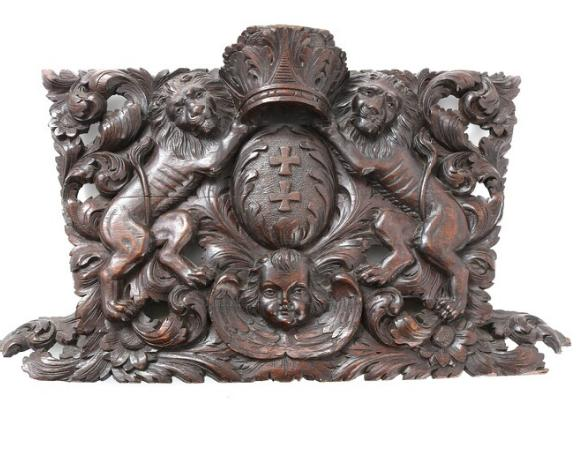 A 20th century dark stained oak carving in the form of coat of arms with crown, lions and cherub