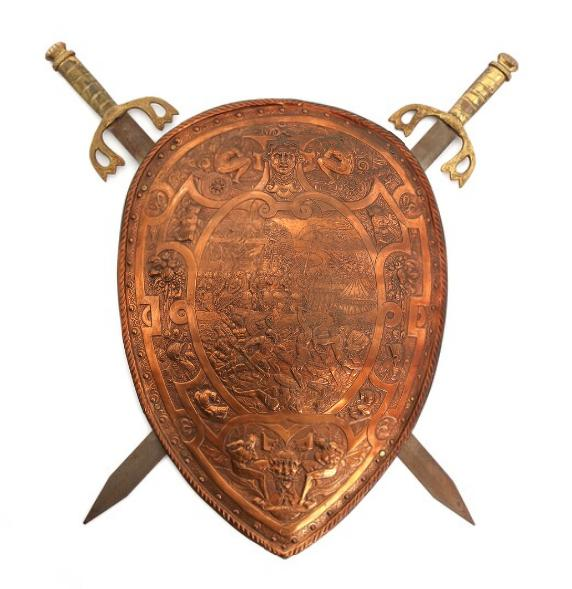 An early 20th century copper crest, embossed in Renaissance style, reverse with two dummy swords