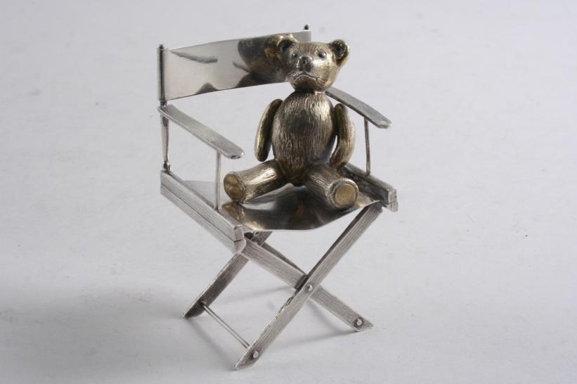 A contemporary parcelgilt novelty or miniature in the form of a Teddy Bear on a director's chair