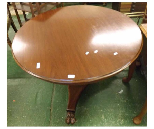 19th century round mahogany dining table, the top raised on a tapering pedestal over three paw-footed base and castors