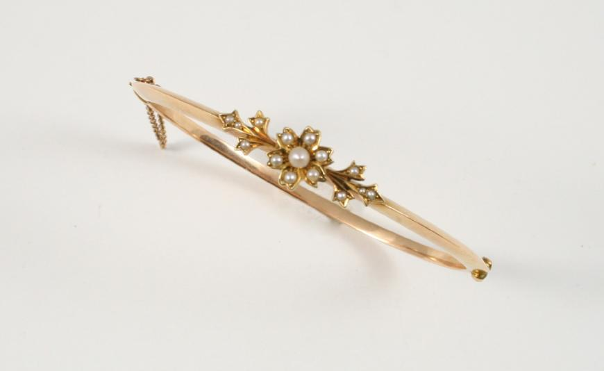 A VICTORIAN GOLD AND PEARL SET HALF HINGED BANGLE