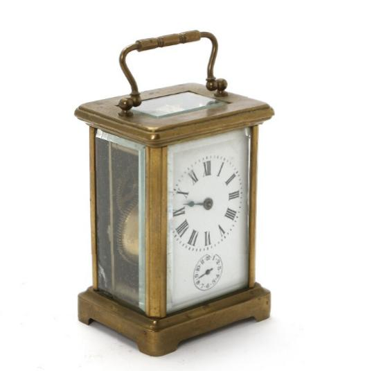 A small French brass carridge clock with cut-glass sides