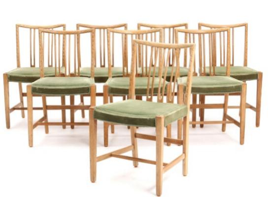 Eight oak side chairs with carvings, seats with green fabric.