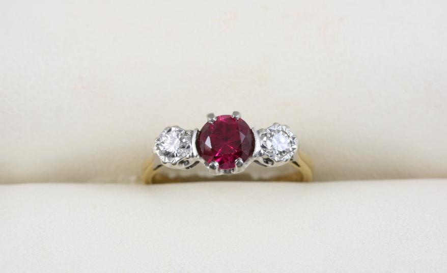A SYNTHETIC RUBY AND DIAMOND THREE STONE RING