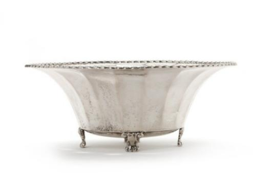 A slightly edged bowl of hammered silver, on four small feet. Beaded upper rim