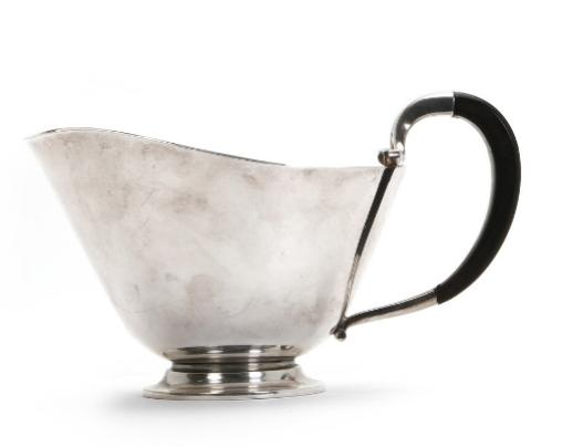 A sterling silver sauce boat with ebony handle