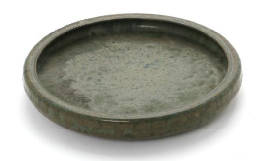 A circular stoneware dish decorated with greyish green glaze