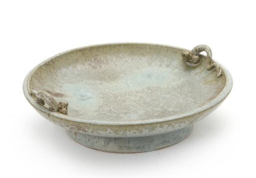 A circular stoneware fruit dish on a circular base