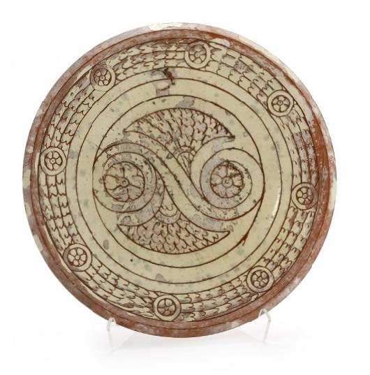 A circular earthenware dish, scratched patterns