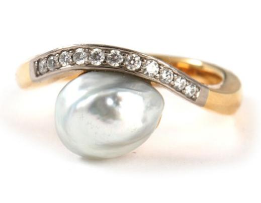 A pearl and diamond ring set with a grey cultured pearl flanked by brilliant-cut diamonds