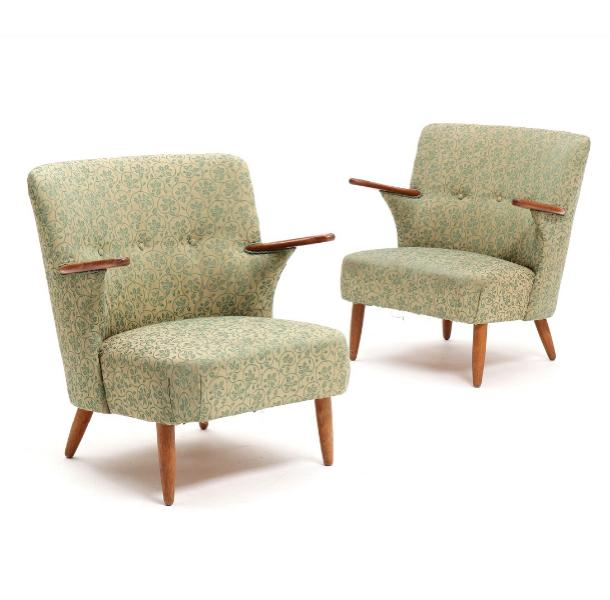 A pair of easy chairs with teak armrests and oak legs