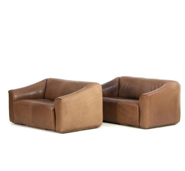 A pair of freestanding sofas upholstered with brown leather