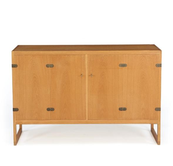 An oak sideboard mounted on runner legs, front with two foldable doors with brass fittings