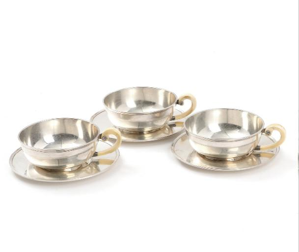 Three Swedish sterling silver bouillon cups and saucers with ivory handles