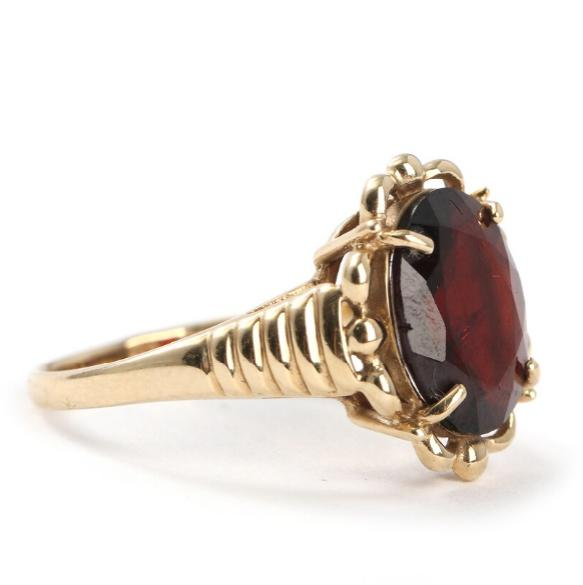 An English garnet ring set with a faceted garnet mounted in 9k gold