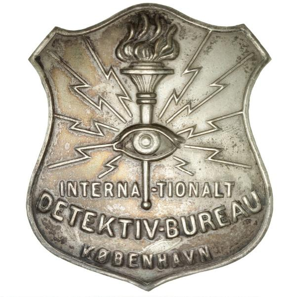"Emblem, ""International Detective Agency, Copenhagen"", 74 x 64 mm"