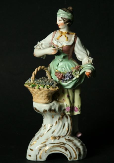 A BERLIN FIGURE OF A FEMALE VINTNER