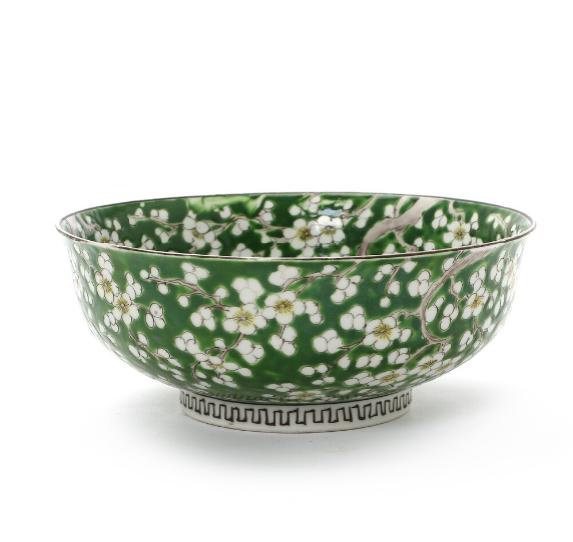A Chinese porcelain bowl decorated with blooming prunus on green ground