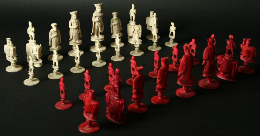 A CHINESE RED AND WHITE EAST AND WEST IVORY COMPOSITE CHESS SET