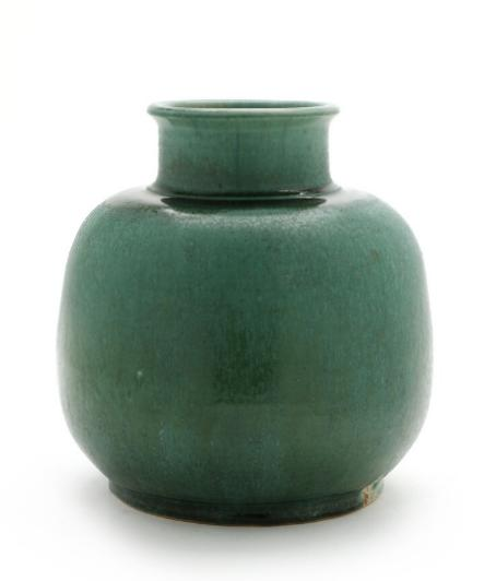 A circular stoneware vase decorated with green glaze