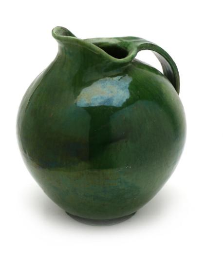 A large stoneware pitcher, decorated with transparent green glaze.