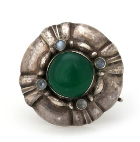 A brooch set with a cabochon agate encircled by four labradorites