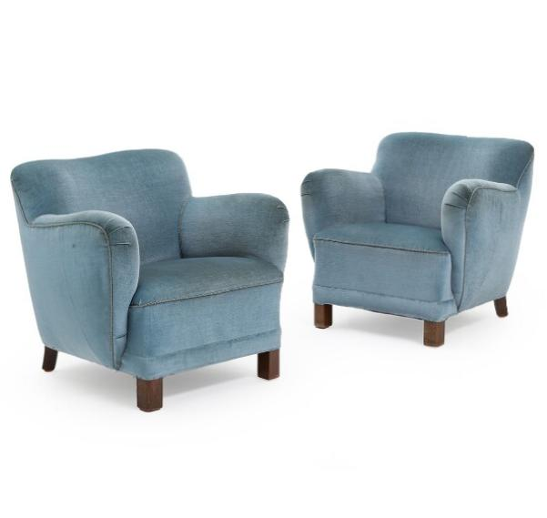 A pair of plump easy chairs upholstered with petrol blue velour
