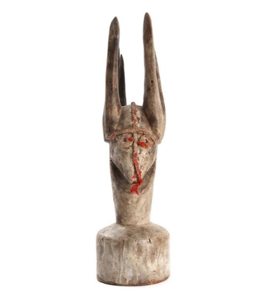 An African patinated carved wood guardian figure, in the shape of a head, decorated with red coloured cord