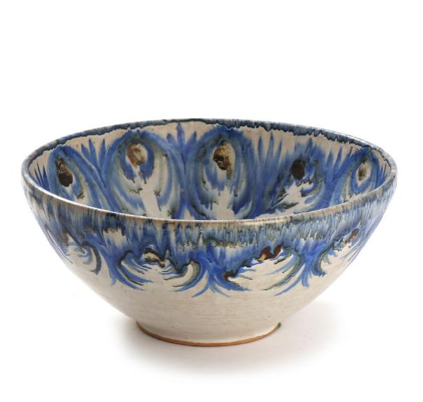 An earthenware bowl decorated with blue and dark glaze on white base